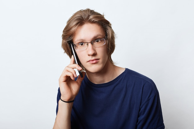 Good-looking male entrepreneur, wearing elegant spectacles, making business call to his partner