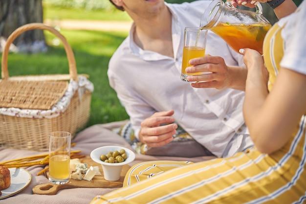 그의 여자 친구가 그 근처에 앉아있는 동안 손에 비 알코올 음료와 함께 좋은 찾고 남성 지주 유리