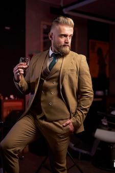 Красивый мужчина в костюме пьет алкоголь, он держит в руках стакан напитка