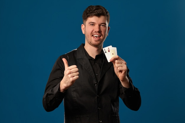 잘 생긴 남자, 포커의 멍청이, 검은 조끼와 셔츠. 두 카드를 들고 웃 고 엄지 표시. 포즈