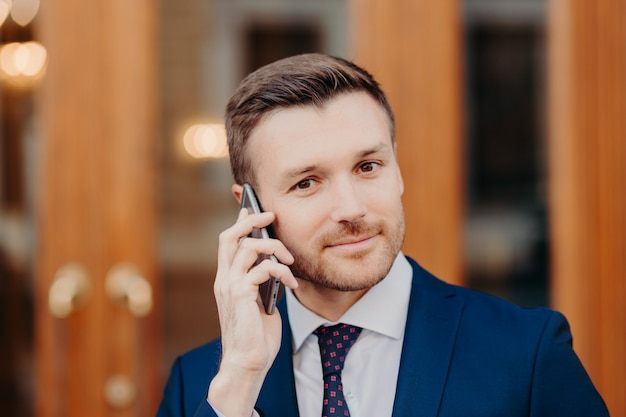 Good looking male with attractive appearance, speaks via cell phone