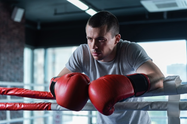 Good-looking man. good-looking strong athletic muscle man standing in boxing ring while working out