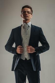 スリーピースのスーツでポーズをとる格好良い男。