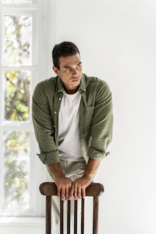 Good-looking man standing near the chair leaning on its back
