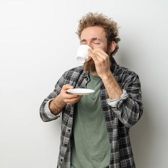 白い壁に分離された格子縞の長袖シャツを着て、巻き毛とひげのコーヒー保持カップを飲む格好良い男