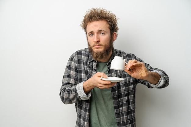 Красивый мужчина с вьющимися волосами и бородой держит перевернутую чашку, показывающую без кофе Premium Фотографии