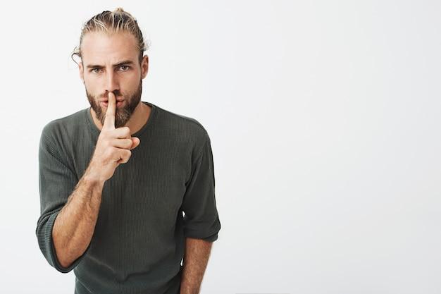 Красивый зрелый парень со стильной прической и бородой держит указательный палец на губах, прося молчать