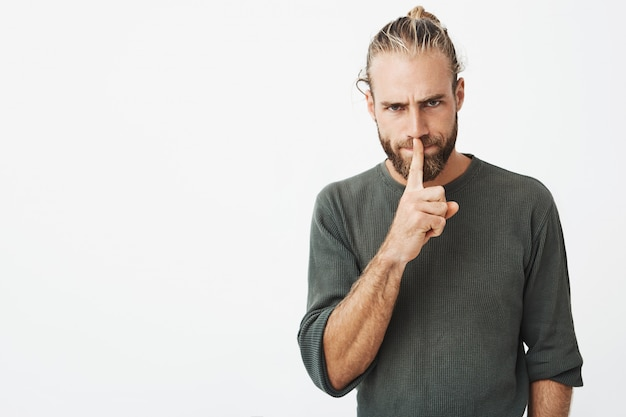 Good-looking mature guy with stylish hairdo and beard holding index finger at lips, asking for silent