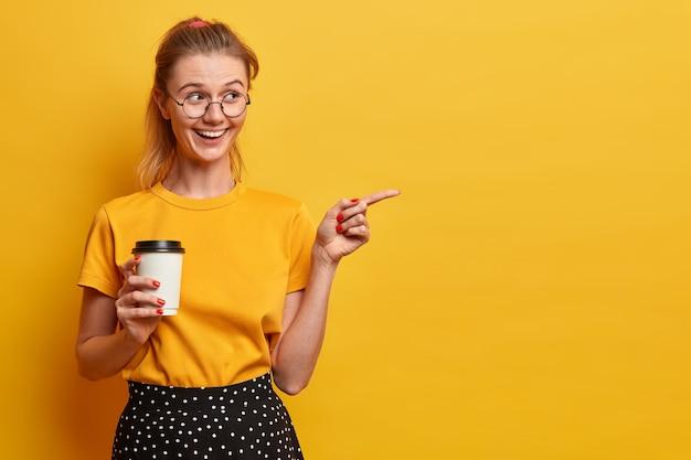 Bella ragazza millenaria indica uno spazio vuoto, invita a fare il check-out, mostra la strada per la pubblicità, tiene un caffè da asporto, indossa grandi occhiali rotondi