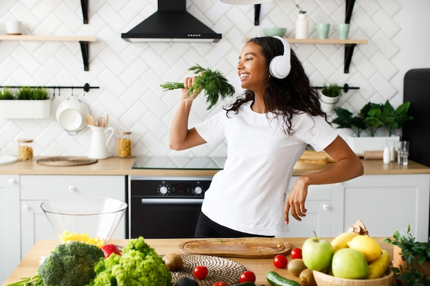 Good-looking mulatto woman in big headphones is smiling and pretending like she is singing in greenery near the table with fresh vegetables and fruits