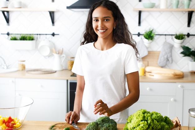 Good-looking mulatto woman is smiling and holding a knife on the modern kitchen dressed in white t-shirt, near the table with fresh vegetables