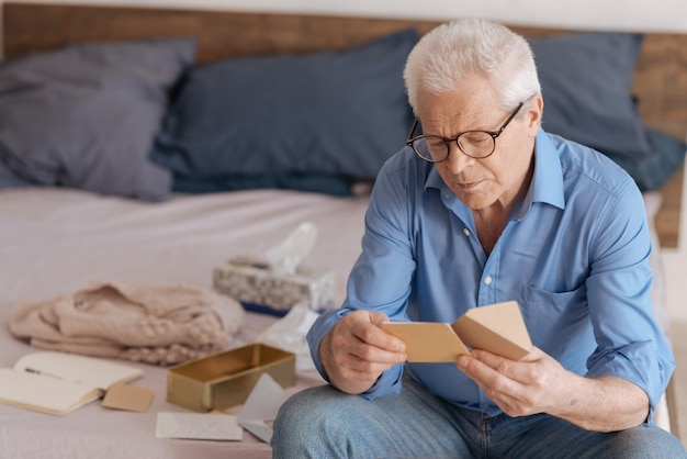 Good looking nice aged man holding a note and reading it while sitting in his bedroom