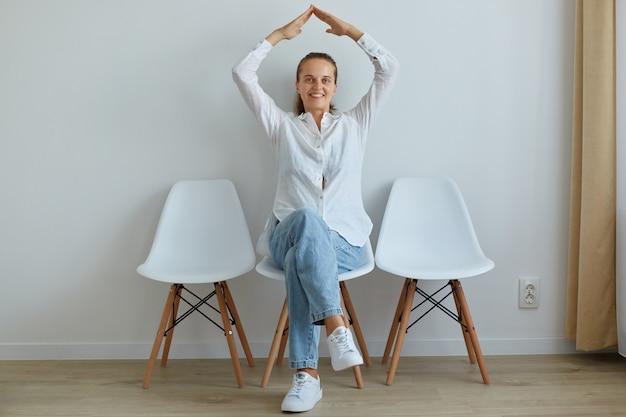 Симпатичная оптимистичная женщина, сидящая на стуле в помещении, в белой рубашке и джинсах, строящая крышу с руками над головой, чувствует себя в безопасности, выражая счастье.