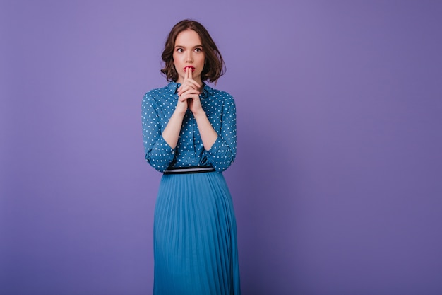 Bella ragazza pensierosa in gonna lunga che guarda lontano durante il servizio fotografico. ritratto dell'interno della signora bruna concentrata isolata sulla parete viola.