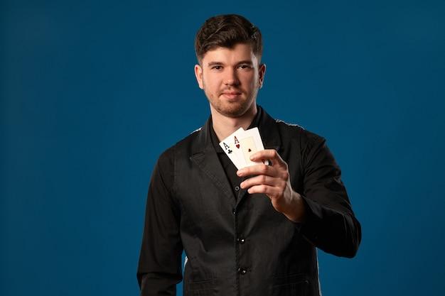 잘 생긴 사람, 포커 초보자, 검은 조끼와 셔츠. 파란색 스튜디오 배경에서 포즈를 취하는 동안 두 개의 카드 놀이, 에이스를 들고 있습니다. 도박, 카지노. 확대.