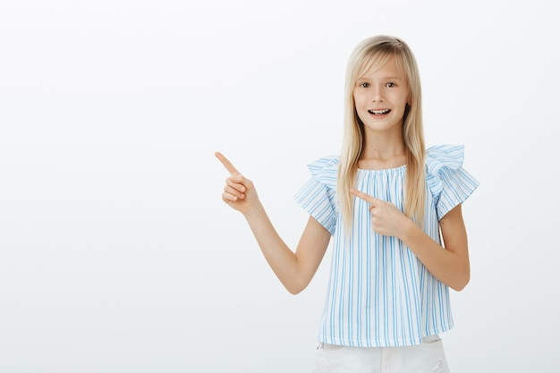 Good-looking pleased young blond child in fashionable blue blouse, feeling excited and amazed while pointing at upper left corner, seeing fascinating and interesting toy over gray wall
