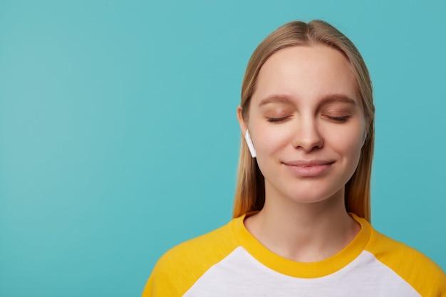 Bella giovane donna dai capelli lunghi bionda soddisfatta che tiene gli occhi chiusi mentre si gode la traccia musicale nei suoi auricolari e sorride leggermente, in posa sul blu