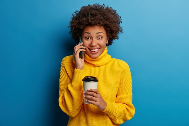 Good looking positive afro american woman has telephone conversation, holds mobile phone near ear