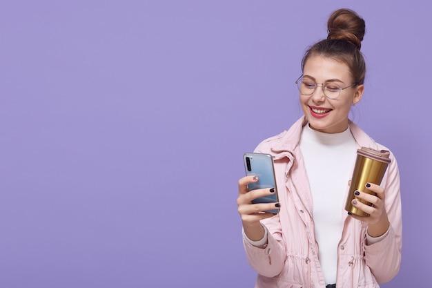 格好良い肯定的な白人女性は携帯電話を手に持って、コーヒーを飲みに行き、楽しそうに笑い、淡いピンクのジャケットを着ています。広告用のスペースをコピーします。