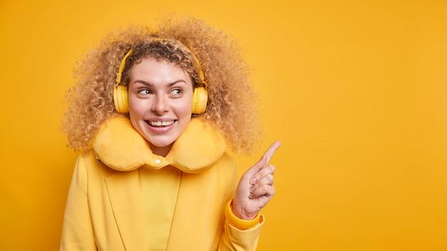 Красиво выглядящая позитивная женщина с густыми кудрявыми волосами привлекает ваше внимание в пространстве для копирования, демонстрирует торговые точки вдали, использует беспроводные наушникиñ– наслаждается плейлистом, носит подушку для шеи для комфорта