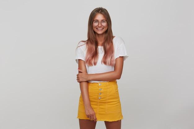 Хорошо выглядящая позитивная молодая длинноволосая блондинка счастливо улыбается, стоя у белой стены, одетая в белую простую футболку и желтую юбку