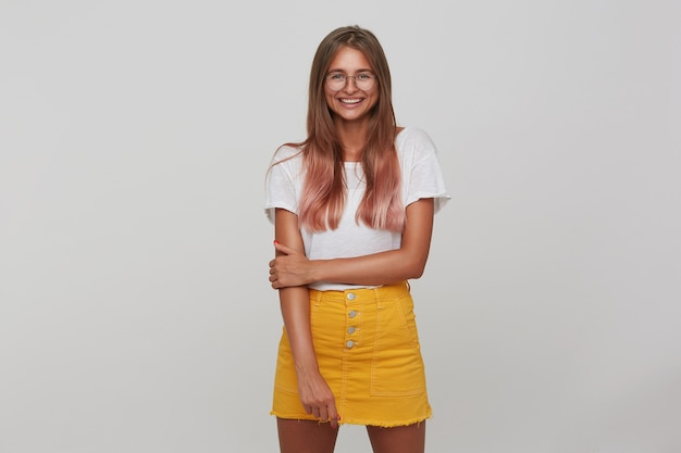 Good looking positive young long haired blonde woman smiling happily while standing over white wall, dressed in white basic t-shirt and yellow skirt