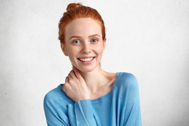 Симпатичная рыжая самка с довольным выражением лица, с широкой улыбкой, рада, что ее продвигают на работе или получают бонус за прилежание, изолированность на белом фоне