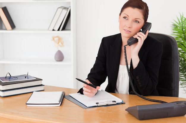 Good looking redhaired woman in suit writing on a notepad and phoning