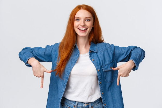 Good-looking redhead female in denim and white shirt