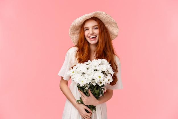 하얀 드레스를 입고 제스처를 보여주는 잘 생긴 빨간 머리 여성.