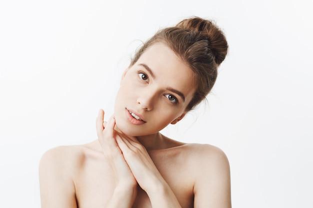 スパの広告のためにポーズをとって、顔の下で手を繋いでいる穏やかな表情で格好良いリラックスしたセクシーなヨーロッパの学生の女の子。コピースペース