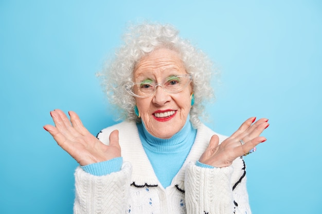 Good looking retired woman spreads palms smiles gently smiles positively wears transparent glasses sweater has bright makeup cares about appearance in old age