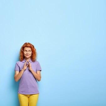 잘 생긴 만족스러운 밀레 니얼 소녀는 여우 같은 머리카락을 가지고 있으며 손가락을 모으고 좋은 의도를 염두에두고 놀라운 일을 할 계획입니다.