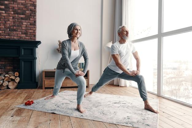 自宅で時間を過ごしながら運動と笑顔のスポーツウェアの格好良い年配のカップル