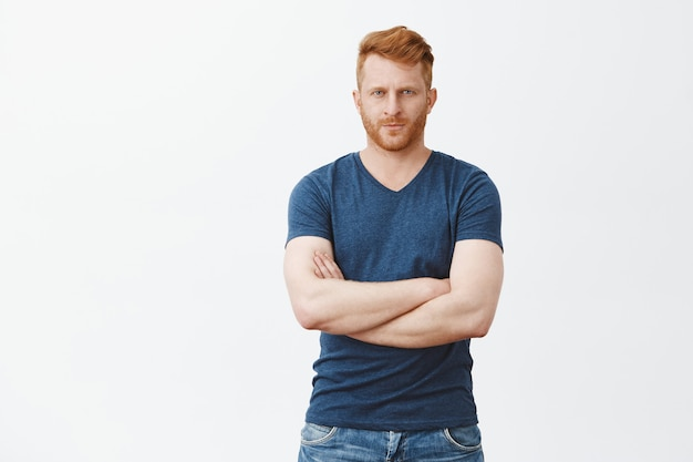 Good-looking serious male bodyguard with red hair and bristle, frowning, looking from under forehead strict, crossing fingers on chest, being strong and masculine, posing over gray wall