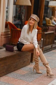 Красивая сексуальная блондинка в белой блузке, кожаной юбке и вязаных бежевых сапогах до бедра.