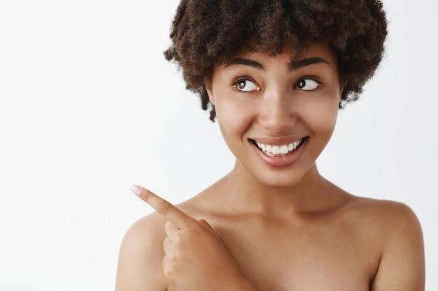 Bella donna afroamericana femminile timida e tenera con i capelli ricci in posa nuda, indicando e guardando nell'angolo in alto a sinistra