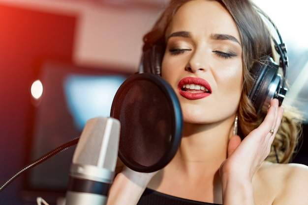 Good-looking singer with headphones in front of microphone sings with her opened mouth in modern studio.