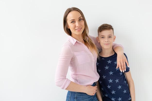 Симпатичная мать-одиночка и сын-подросток на белом фоне. сплоченность, дружба и семья
