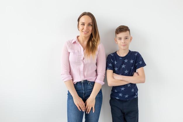 Симпатичная мать-одиночка и сын-подросток на белой стене