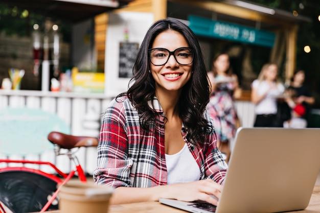 Симпатичная умная девушка позирует с улыбкой на улице. удивительная брюнетка женщина, использующая ноутбук в выходные утром.