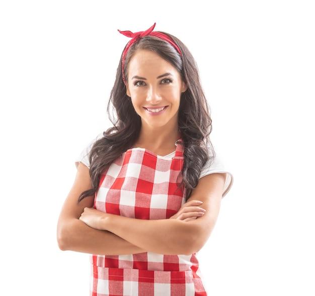彼女の胸に腕を組んで孤立した白い背景に自信を持って立っている格好良い笑顔のブルネット料理人。赤と白のチェックのエプロンと髪の毛に赤いリボンを着ています。