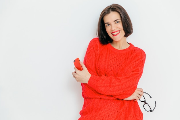 Good looking smiling brunette female with dark hair, wears red knitted sweater, holds glasses and modern smart phone