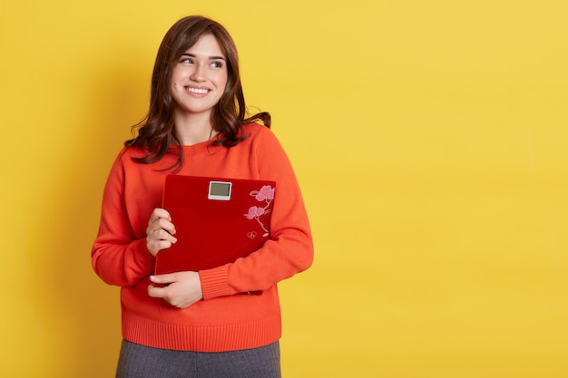 Good looking smiling brunette woman in orange casual sweater embracing floor scales and looking away with dreamy expression, isolated over yellow wall.