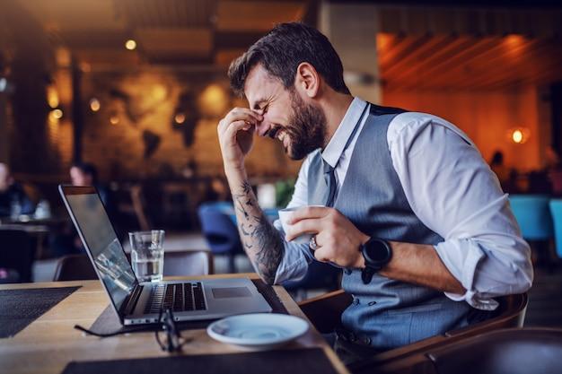 ハンサムな笑顔の白人ひげを生やした実業家のスーツのカフェに座って、コーヒーカップを押しながら笑っています。テーブルの上にはグラス、ラップトップ、水があります。