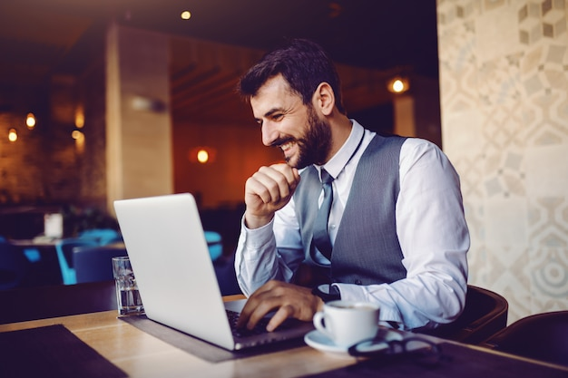Good-looking smiling caucasian elegant bearded businessman in suit sitting in cafe and using laptop. on table are laptop, coffee, coffee and water.