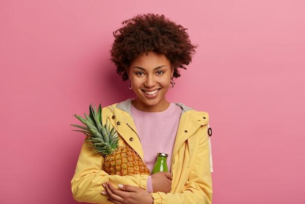 La bella donna sorridente abbraccia l'ananas maturo e una bottiglia di vetro di frullato verde, ha un'espressione positiva, un'alimentazione sana e vitamine