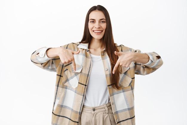 Bella donna sorridente che punta il dito verso il basso sul banner, mostra il logo o l'offerta promozionale, consiglia di visitare il negozio, in piedi sul muro bianco