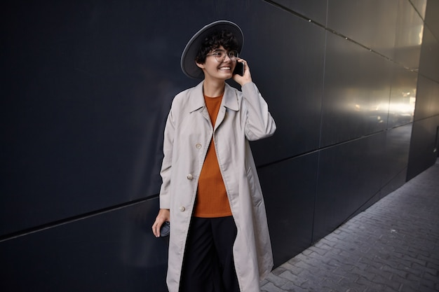 Bella giovane signora bruna riccia sorridente che ha una piacevole conversazione sul telefono mentre posa sopra il muro urbano nero, indossando abiti eleganti e largo cappello grigio