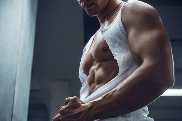 格好良いスポーティーな若い男は彼のシャツをはぎ取ります。フィットネスとボディービルのコンセプト
